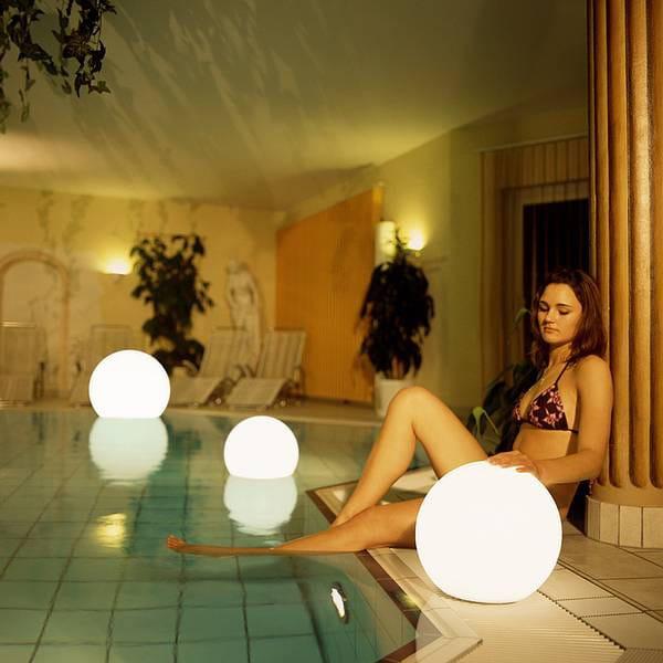 Moonlight Vollkugel Akku-Schwimmleuchte BMWV Weiß Ambiente Pool Innen Frau mit Leuchte am Poolrand