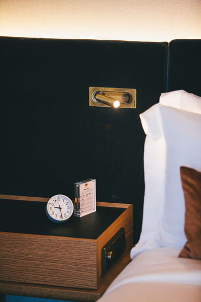 marset Wandleuchte Ledtube RSC Bronze Ambiente Hotelbett asiatisch linke Seite